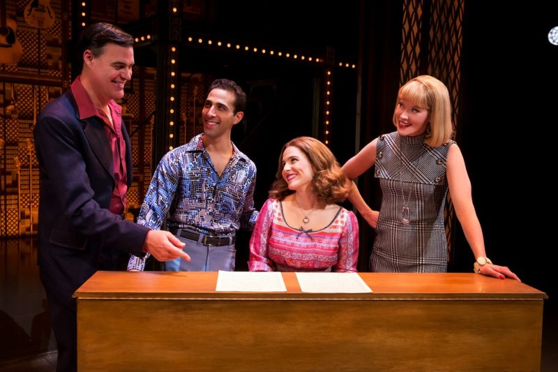 """The principal actors of the musical performing """"You've Got a Friend"""" around a piano with the actress playing Carole King at the keys."""