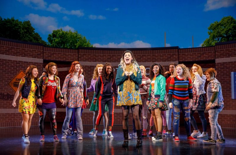 Janis (Barrett Wilbert Reed) and the girls of North Shore High School stand outside the school in protest and in a moment of empowerment in a scene from Mean Girls