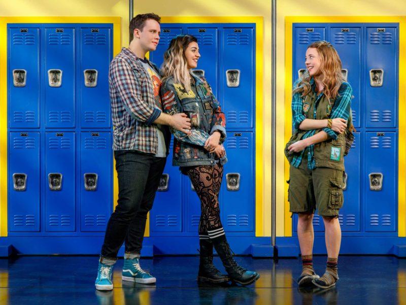 A scene from Mean Girls where Damian (Grey Henson) and Janis (Barrett Wilbert Weed) meet Cady (Erika Henningsen) in the school hallway.