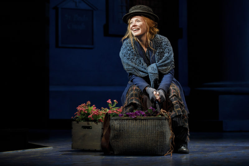 Eliza, dressed in rags and dirt, sits hopefully on next to her basket of flowers.
